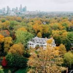 Aerial shot of Duke mansion surrounded by trees with a city skyline in the background