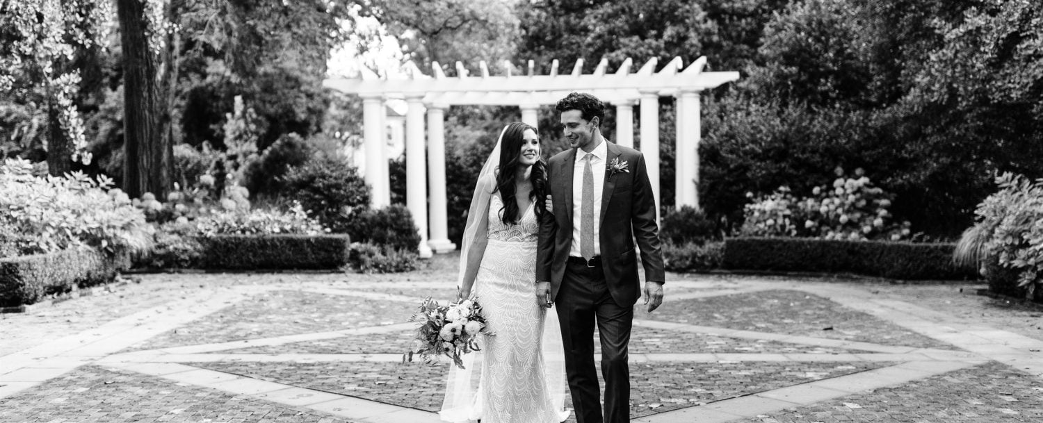 A bride and groom in front of a pergola.