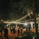 A rehearsal dinner in the courtyard beneath hanging lights.