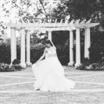 A bride poses in front of a pergola.