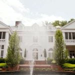 The front of Duke Mansion, with a fountain spraying water upward.
