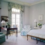 Ornate bedroom with green-and-white patterned curtains.