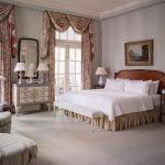 Ornate bedroom at Duke Mansion with fine curtains and doors to an outer porch.